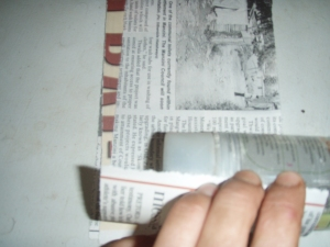 3. Lay your form (the cylindrical container you gathered) off-center on the newspaper.